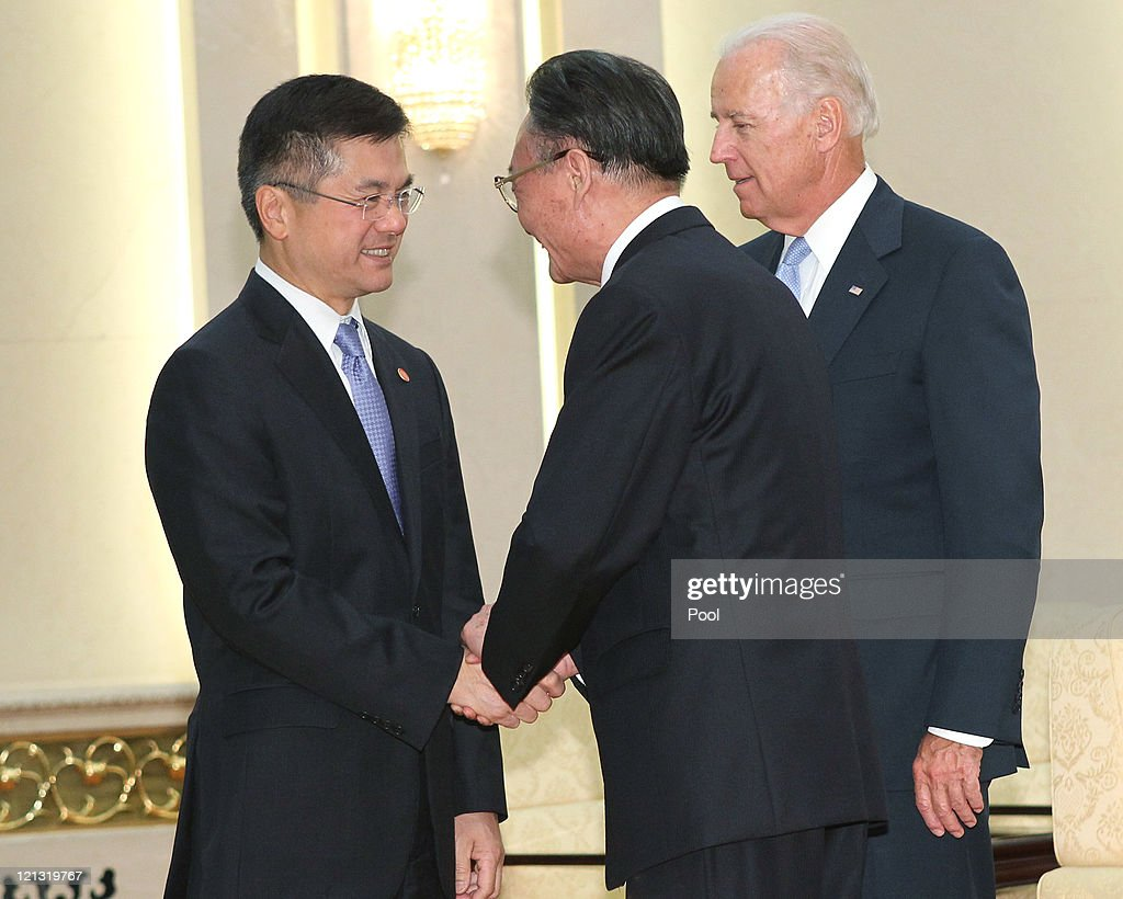 Vice President Joe Biden looks on as US ambassador to China Gary Locke shakes hands with Chinese National Peoples Congress Standing Committee...