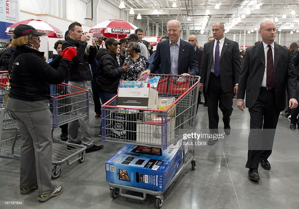 US Vice President Joe Biden pushes a full shopping cart during a visit to a Costco store in Washington, DC, on November 29, 2012, to purchase Christmas gifts. Biden made the visit to the first Costco store located in Washington, DC, during its grand opening. AFP PHOTO / Saul LOEB