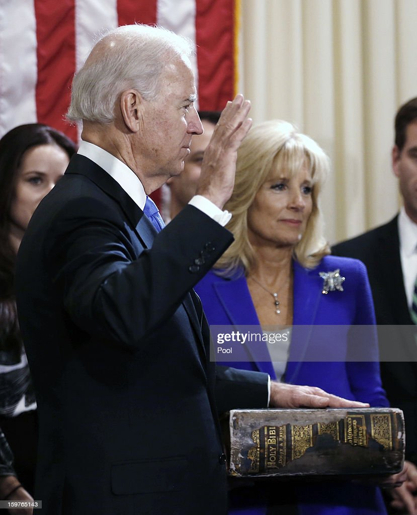 U.S. Vice President Joe Biden (L) takes the oath of office as his wife Dr. Jill Biden (R) looks on during the official swearing-in ceremony at the Naval Observatory on January 20, 2013 in Washington, DC. Biden and U.S. President Barack Obama will be officially sworn in a day before the ceremonial inaugural swearing-in.