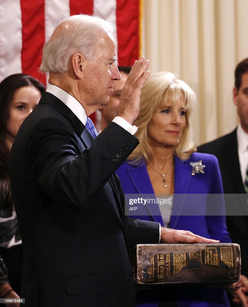 US Vice President Joe Biden (L) takes the oath of office from Supreme Court Justice Sonia Sotomayor as his wife Jill Biden holds the family bible while family members look on at the US Naval Observatory in Washington on January 20, 2013. AFP PHOTO/POOL/Kevin Lamarque
