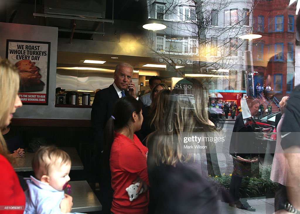 Vice President Joe Biden (C) talks on his cell phone in a crowd of customers while picking up his lunch at Capriotti's sandwhich shop, on November 21, 2013 in Washington, DC. Capriotti's is a Delaware based Italian hoagie chain and a favorite of the Vice President.