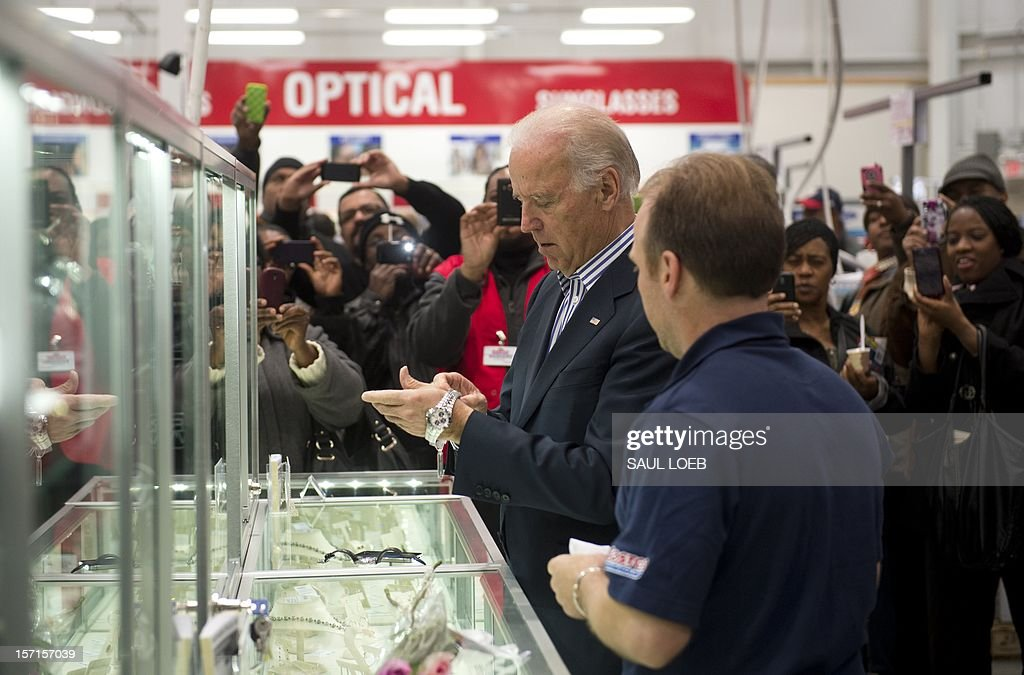 US Vice President Joe Biden tries on a watch during a visit to a Costco store on a shopping trip in Washington, DC, on November 29, 2012. Biden made the visit to the first Costco store located in Washington, DC, during its grand opening. AFP PHOTO / Saul LOEB