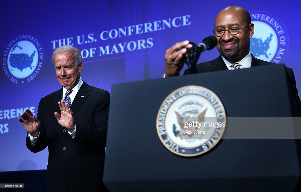 U.S. Vice President <a gi-track='captionPersonalityLinkClicked' href=/galleries/search?phrase=Joseph+Biden&family=editorial&specificpeople=206897 ng-click='$event.stopPropagation()'>Joseph Biden</a> (L) acknowledges the audience as he is introduced by U.S. Conference of Mayors President and Mayor of Philadelphia <a gi-track='captionPersonalityLinkClicked' href=/galleries/search?phrase=Michael+Nutter&family=editorial&specificpeople=4695146 ng-click='$event.stopPropagation()'>Michael Nutter</a> (R) during opening plenary luncheon of the 81st Winter Meeting of the USCM at Capital Hilton Hotel January 17, 2013 in Washington, DC. The meeting will focus on various topics including job creation, fiscal cliff agreement and sequestration, gun control, threat to tax-exempt financing, Superstorm Sandy response, and immigration.