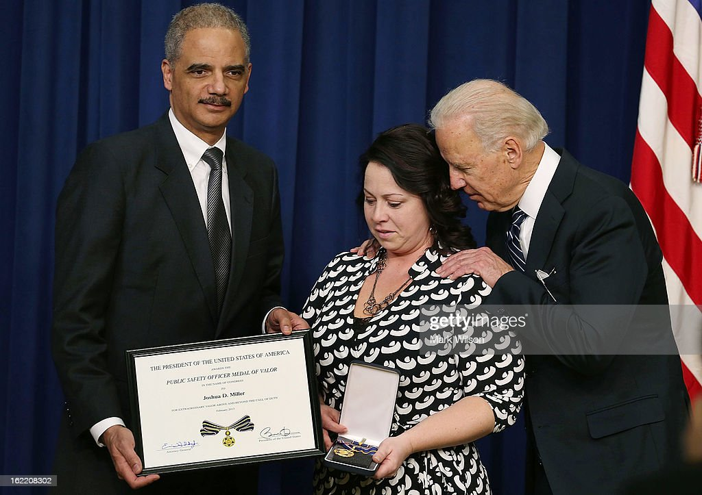 U.S. Vice President <a gi-track='captionPersonalityLinkClicked' href=/galleries/search?phrase=Joseph+Biden&family=editorial&specificpeople=206897 ng-click='$event.stopPropagation()'>Joseph Biden</a> (R) and Attorney General <a gi-track='captionPersonalityLinkClicked' href=/galleries/search?phrase=Eric+Holder&family=editorial&specificpeople=1060367 ng-click='$event.stopPropagation()'>Eric Holder</a> (L) give the Medal of Valor to Angela Miller, widow of fallen Pennsylvania State Trooper Joshua D. Miller, during an event in Eisenhower Executive Office Building, February 20, 2013 in Washington, DC. Vice President Biden presented the award to public safety officers who have exhibited exceptional courage, regardless of personal safety, in the attempt to save or protect others from harm.