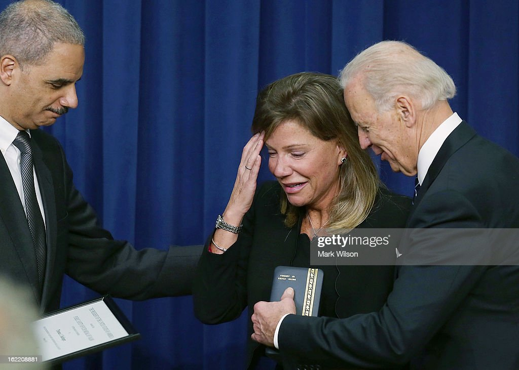 U.S. Vice President <a gi-track='captionPersonalityLinkClicked' href=/galleries/search?phrase=Joseph+Biden&family=editorial&specificpeople=206897 ng-click='$event.stopPropagation()'>Joseph Biden</a> (R) and Attorney General <a gi-track='captionPersonalityLinkClicked' href=/galleries/search?phrase=Eric+Holder&family=editorial&specificpeople=1060367 ng-click='$event.stopPropagation()'>Eric Holder</a> (L) give the Medal of Valor to Paige Baitinger, widow of fallen Police officer Thomas Baitinger of St. Petersburg, Florida, during an event in Eisenhower Executive Office Building, February 20, 2013 in Washington, DC. Vice President Biden presented the award to public safety officers who have exhibited exceptional courage, regardless of personal safety, in the attempt to save or protect others from harm.