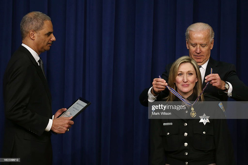 Vice President Joseph Biden (R) and Attorney General <a gi-track='captionPersonalityLinkClicked' href=/galleries/search?phrase=Eric+Holder&family=editorial&specificpeople=1060367 ng-click='$event.stopPropagation()'>Eric Holder</a> (L) give the Medal of Valor to Deputy Sheriff Krista McDonald of the Kitsap County Washington Sheriff's Office, during an event in Eisenhower Executive Office Building, February 20, 2013 in Washington, DC. Vice President Biden presented the award to public safety officers who have exhibited exceptional courage, regardless of personal safety, in the attempt to save or protect others from harm.