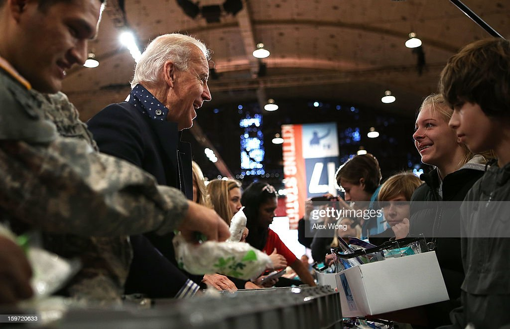U.S. Vice President <a gi-track='captionPersonalityLinkClicked' href=/galleries/search?phrase=Joseph+Biden&family=editorial&specificpeople=206897 ng-click='$event.stopPropagation()'>Joseph Biden</a> (2nd L) chats with volunteers as he participates during a Unite America in Service event on the National Day of Service as part of the 57th Presidential Inauguration January 19, 2013 at the DC Armory in Washington, DC. Vice President Biden and his family joined volunteers to pack care kits filled with necessities for deployed U.S. Service Members, Wounded Warriors, Veterans and First Responders.