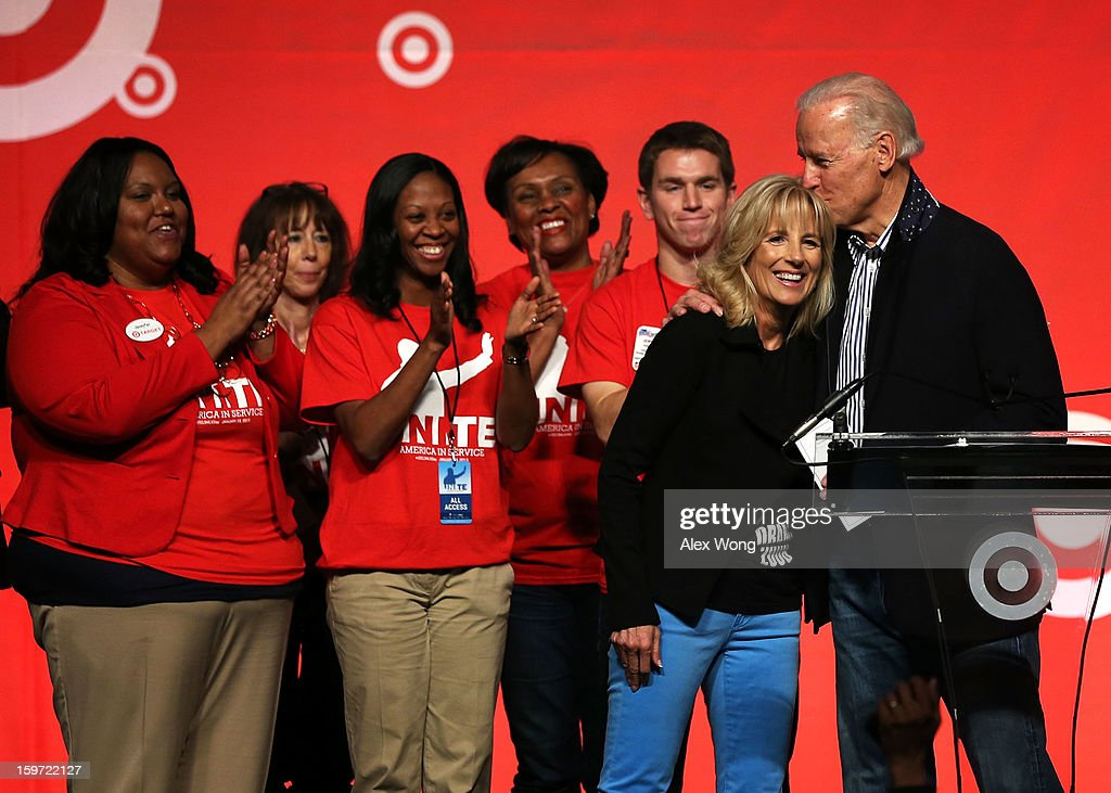 U.S. Vice President <a gi-track='captionPersonalityLinkClicked' href=/galleries/search?phrase=Joseph+Biden&family=editorial&specificpeople=206897 ng-click='$event.stopPropagation()'>Joseph Biden</a> (R) kisses his wife <a gi-track='captionPersonalityLinkClicked' href=/galleries/search?phrase=Jill+Biden&family=editorial&specificpeople=997040 ng-click='$event.stopPropagation()'>Jill Biden</a> (2nd R) as volunteers look on during a Unite America in Service event on the National Day of Service as part of the 57th Presidential Inauguration January 19, 2013 at the DC Armory in Washington, DC. Vice President Biden and his family joined volunteers to pack care kits filled with necessities for deployed U.S. Service Members, Wounded Warriors, Veterans and First Responders.