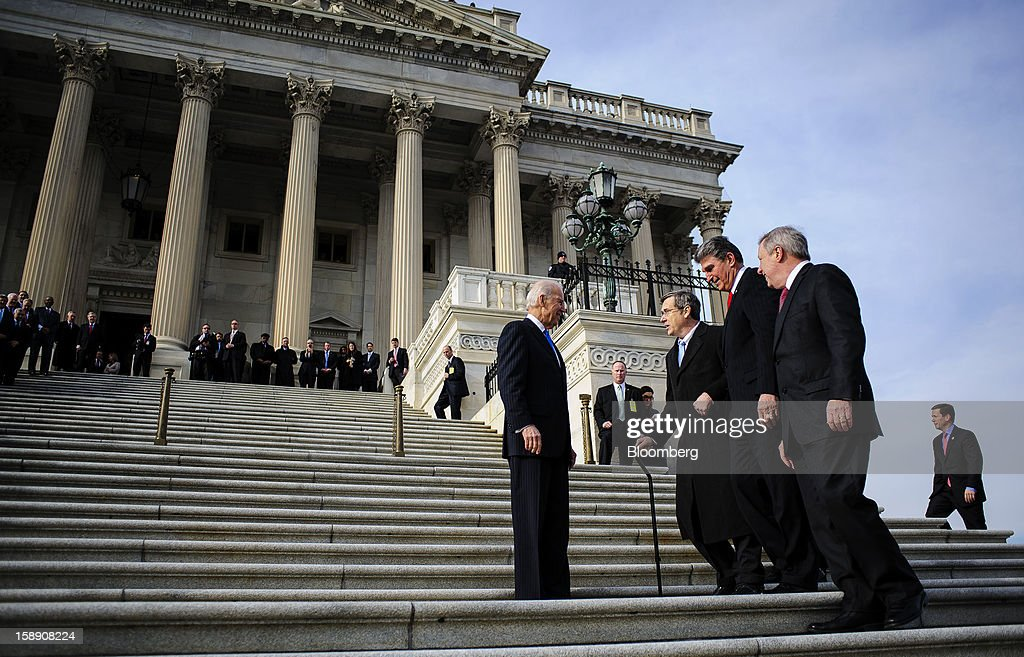 U.S. Vice President Joseph 'Joe' Biden, left, greets Senator <a gi-track='captionPersonalityLinkClicked' href=/galleries/search?phrase=Joe+Manchin&family=editorial&specificpeople=568465 ng-click='$event.stopPropagation()'>Joe Manchin</a>, a Democrat from West Virginia, second right, and Senator <a gi-track='captionPersonalityLinkClicked' href=/galleries/search?phrase=Mark+Kirk&family=editorial&specificpeople=2707485 ng-click='$event.stopPropagation()'>Mark Kirk</a>, a Republican from Illinois, second left, on the steps of the U.S. Capitol in Washington, D.C., U.S., on Thursday, Jan. 3, 2013. Kirk returned for the first time since he suffered a stroke on Jan. 23, 2012. The 113th Congress convenes today in Washington where new members will try to meld their diverse backgrounds in a legislature containing a record seven openly gay lawmakers, an unprecedented 20 women in the Senate and the first all-female state delegation, from New Hampshire. Photographer: Pete Marovich/Bloomberg via Getty Images