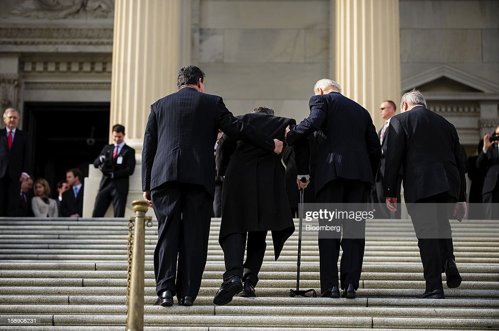 U.S. Vice President Joseph 'Joe' Biden, second right, and Senator <a gi-track='captionPersonalityLinkClicked' href=/galleries/search?phrase=Joe+Manchin&family=editorial&specificpeople=568465 ng-click='$event.stopPropagation()'>Joe Manchin</a>, a Democrat from West Virginia, left, assist Senator <a gi-track='captionPersonalityLinkClicked' href=/galleries/search?phrase=Mark+Kirk&family=editorial&specificpeople=2707485 ng-click='$event.stopPropagation()'>Mark Kirk</a>, a Republican from Illinois, second left, up the steps of the U.S. Capitol in Washington, D.C., U.S., on Thursday, Jan. 3, 2013. Kirk returned for the first time since he suffered a stroke on Jan. 23, 2012. The 113th Congress convenes today in Washington where new members will try to meld their diverse backgrounds in a legislature containing a record seven openly gay lawmakers, an unprecedented 20 women in the Senate and the first all-female state delegation, from New Hampshire. Photographer: Pete Marovich/Bloomberg via Getty Images