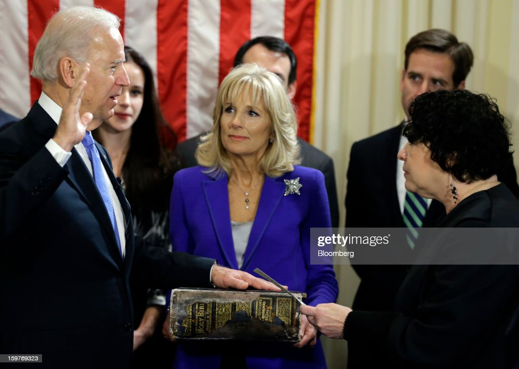 U.S. Vice President Joseph 'Joe' Biden, with his wife <a gi-track='captionPersonalityLinkClicked' href=/galleries/search?phrase=Jill+Biden&family=editorial&specificpeople=997040 ng-click='$event.stopPropagation()'>Jill Biden</a>, center, holding the Biden family Bible, is sworn in by Supreme Court Justice <a gi-track='captionPersonalityLinkClicked' href=/galleries/search?phrase=Sonia+Sotomayor&family=editorial&specificpeople=5872777 ng-click='$event.stopPropagation()'>Sonia Sotomayor</a>, right, during an official ceremony at the Naval Observatory in Washington, D.C., U.S., on Sunday, Jan. 20, 2013. U.S. President Barack Obama is also set to take the oath of office later today surrounded by close friends and advisers in a small ceremony at the White House that will officially begin his second term in office Photographer: Josh Haner/Pool via Bloomberg