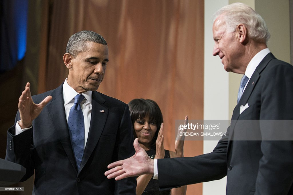 US Vice President Joseph R. Biden reaches out to shake US President Barack Obama's hand during an inauguration reception at the National Building Museum January 20, 2013 in Washington, DC. US President Barack Obama and US Vice President Joseph R. Biden, who were officially worn in for their second term earlier today, will participate in a ceremonial inauguration on Monday. AFP PHOTO/Brendan SMIALOWSKI