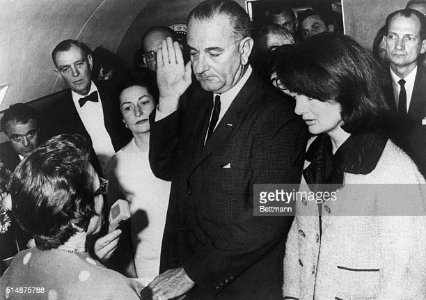 Vice President Lyndon B Johnson is sworn in to the office of the Presidency aboard Air Force One in Dallas Texas hours after the assassination of...