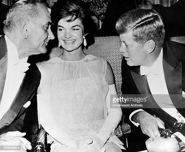 Vice President Lyndon Johnson leans over Jacqueline Kennedy to listen to President John Kennedy at the inaugural ball after their election to office...