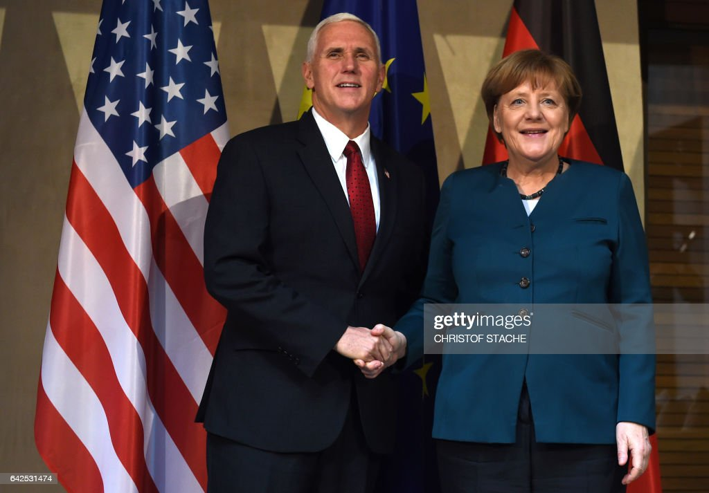 US Vice President Michael Richard Pence (L) and German Chancellor Angela Merkel shake hands during a photo call prior to a bilateral meeting on the 2nd day of the 53rd Munich Security Conference (MSC) at the Bayerischer Hof hotel in Munich, southern Germany, on February 18, 2017. / AFP / Christof STACHE