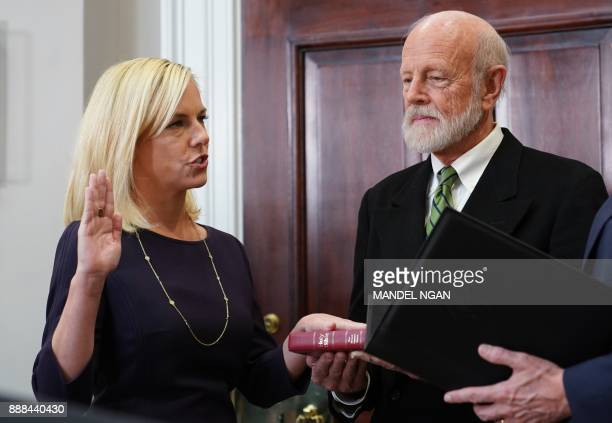 US Vice President Mike Pence administers the oath of office to Homeland Security Secretary Kirstjen Nielsen in the Roosevelt Room of the White House...