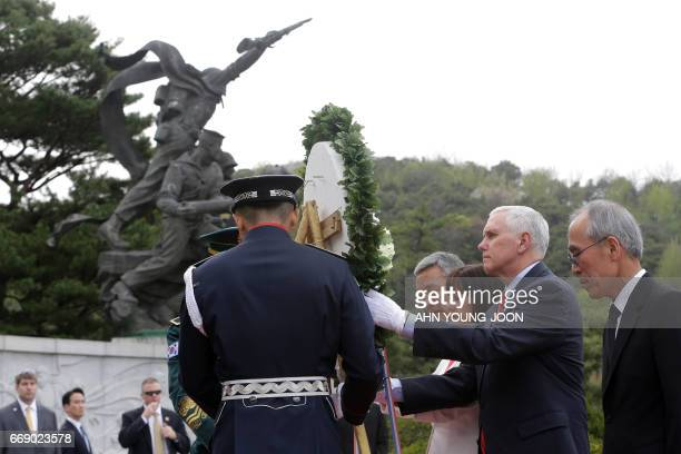 US Vice President Mike Pence and his wife Karen carry a wreath at the National Cemetery in Seoul on April 16 2017 Pence arrived in South Korea for a...
