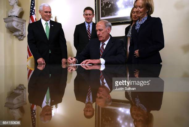 S Vice President Mike Pence and Marsha Coats look on as National Intelligence Director Dan Coats signs paperwork during his swearingin cerermony at...