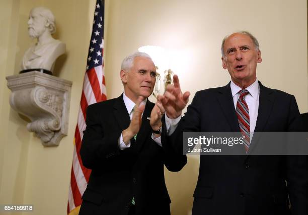 S Vice President Mike Pence applauds new National Intelligence Director Dan Coats during Coats' swearingin ceremony at the US Capitol on March 16...