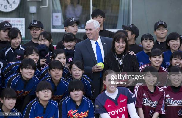 US Vice President Mike Pence center and second lady Karen Pence center right pose for photographs with baseball and softball players as they visit a...