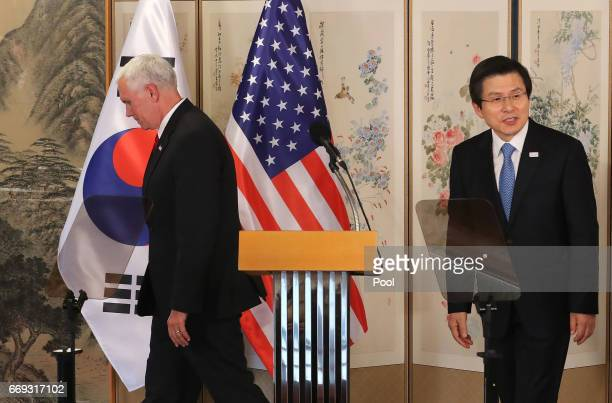 US Vice President Mike Pence leaves with South Korean acting president and prime minister Hwang Kyoahn after their joint press conference on April 17...