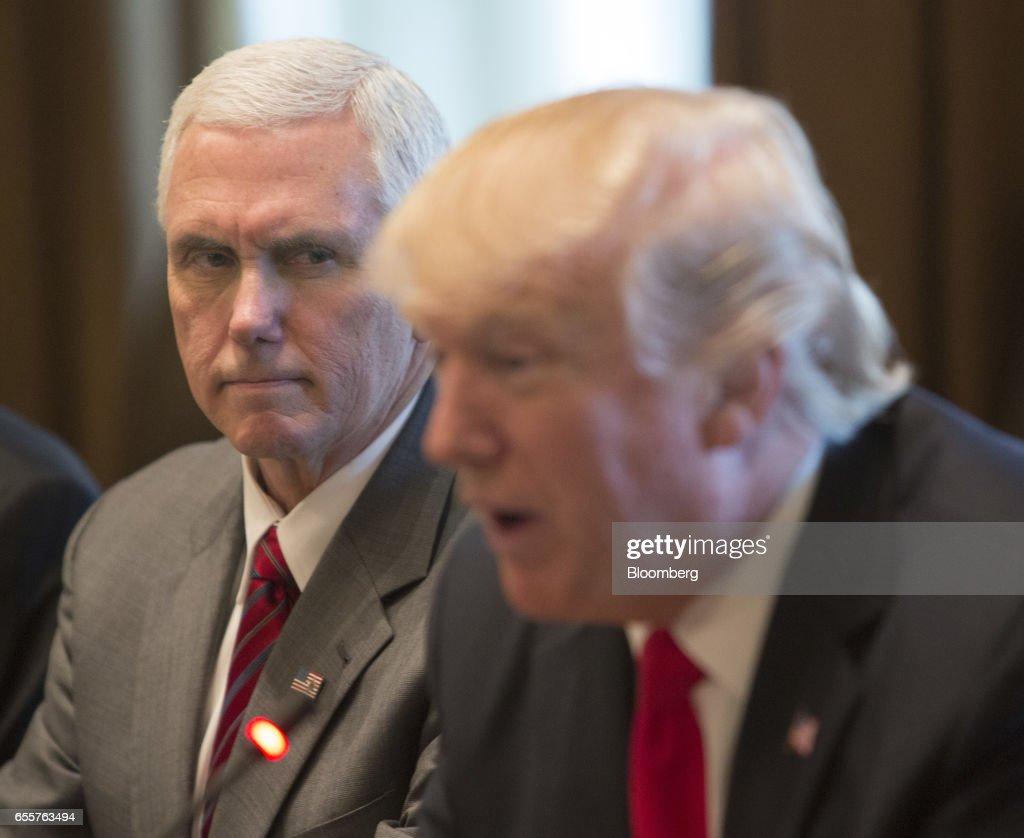 U.S. Vice President Mike Pence, left, listens as U.S. President Donald Trump, speaks during a meeting with Haider al-Abadi, Iraq's prime minister, not pictured, at the White House in Washington, D.C., U.S., on Monday, March 20, 2017. Trump used a White House meeting with al-Abadi to criticize both his immediate predecessors' military strategies in the country. Photographer: Chris Kleponis/Pool via Bloomberg
