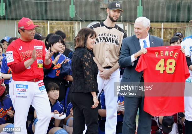 US Vice President Mike Pence receives a baseball uniform while meeting Japanese junior and senior high school students who play baseball and softball...