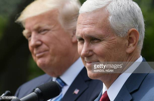 US Vice President Mike Pence speaks while standing next to US President Donald Trump during a ceremony before the signing of an Executive Order on...