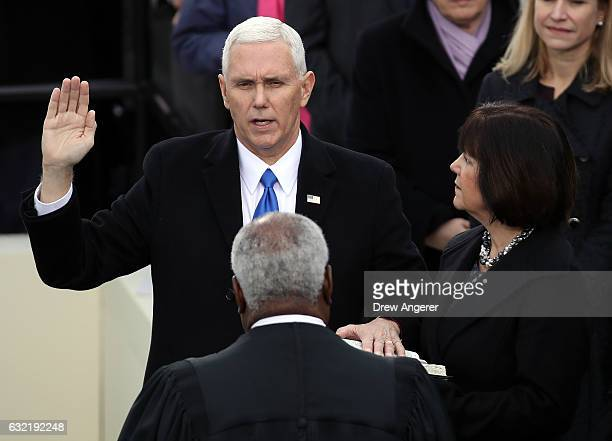 S Vice President Mike Pence takes the oath of office from Supreme Court Justice Clarence Thomas as his wife Karen Pence looks on on the West Front of...