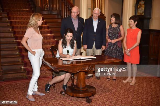 US Vice President Mike Pence watches his daughter Audrey sign the visitors book at Government House along with his daughter Charlotte and wife Karen...