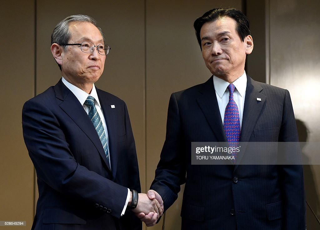 Vice President of Japan's Toshiba Corporation Satoshi Tsunakawa (L) shakes hands with Vice President Shigenori Shiga (R) during a press conference at the headquarters in Tokyo on May 6, 2016. Tsunakawa will assume new Toshiba president and Shiga will be chairman after the shareholders meeting in June. / AFP / TORU