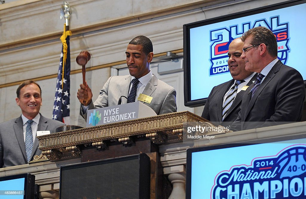 Vice President Robert Power, Connecticut Huskies Men's basketball Coach Kevin Ollie, University of Connecticut Director of Athletics Warde Manuel, and Connecticut Huskies Women's basketball coach Geno Auriemma ring the closing bell at New York Stock Exchange on April 10, 2014 in New York City.