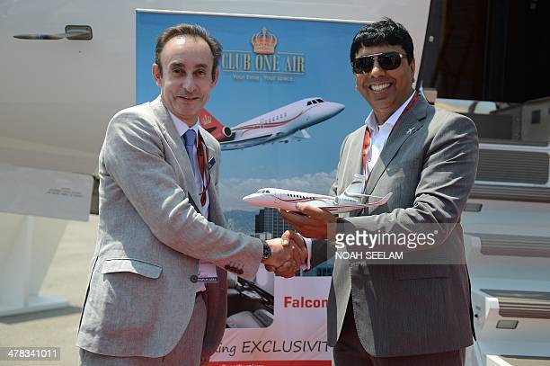 Vice President Sales Dassault Aviation Gilles Gautier shakes hands as he delivers a Falcon 2000 LX Business Jet to customer Chief Executive Officer...