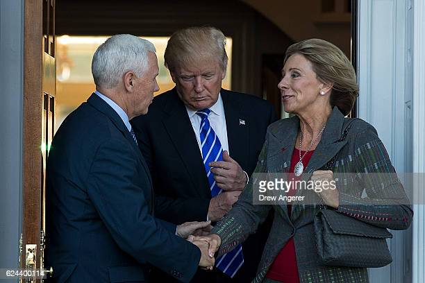 Vice presidentelect Mike Pence presidentelect Donald Trump and Betsy DeVos leave the clubhouse after their meeting at Trump International Golf Club...