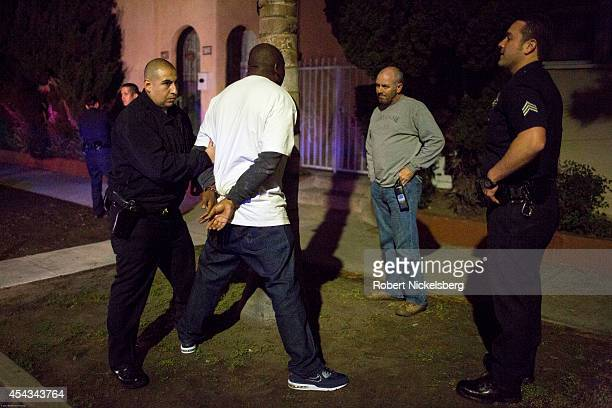 A vice squad officer with the Los Angeles Police Department Sergeant Brian Gallagher right speaks to a handcuffed man February 1 2013 before he's...