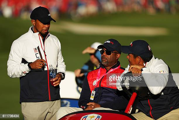 Vicecaptain Tiger Woods of the United States looks on with Darius Rucker and Notah Begay III during morning foursome matches of the 2016 Ryder Cup at...