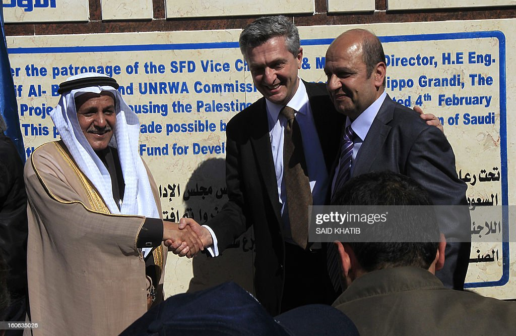 Vice-Chairman and Managing Director of the Saudi Fund for Development (SFD), Yousef al-Bassam (L) shakes hands with UNRWA's Commissioner-General Filippo Grandi (C) near UNRWA's chief of the infrastructure and Camp Improvement Department, Munir Manneh (R) during the houses handover ceremony in Rafah, southern Gaza Strip, on February 4, 2013. 750 housing units were built for Palestinian families who lost their home during Israeli military operations in 2004 and 2005 as part of a re-housing Saudi-funded project led by the United Nations Relief and Works Agency for Palestine Refugees (UNRWA). KHATIB