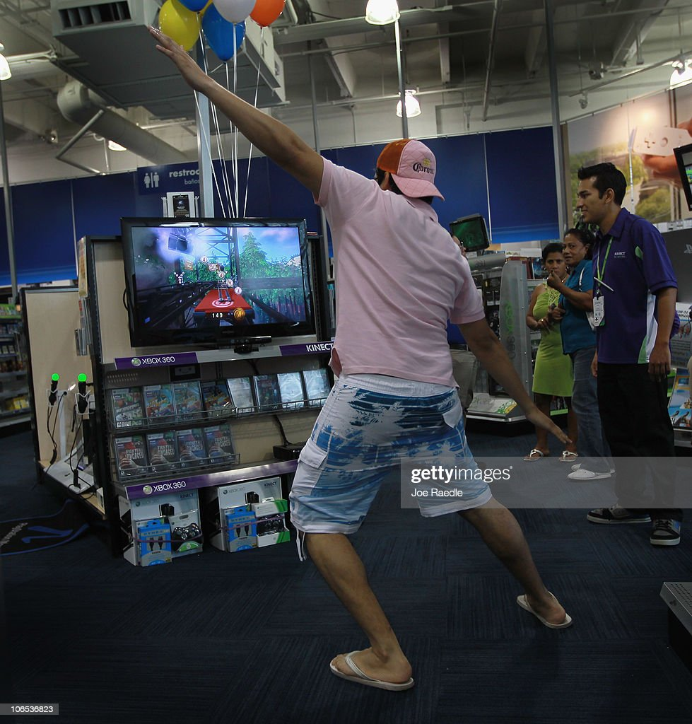 Vicente Galarza plays with Microsoft's new Kinect controller for the Xbox 360 as the Xbox representative Charles Leano (R) looks on at the Best Buy store on November 4, 2010 in Miami Beach, Florida. The Kinect went on sale today and uses sensors to read the players body language so controllers are not necessary to play Xbox games with the Kinect.