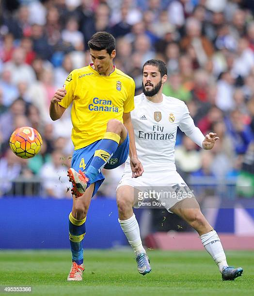 Vicente Gomez of UD Las Plamas passes the ball beside Isco of Real Madrid during the La Liga match between Real Madrid CF and UD Las Palmas at...