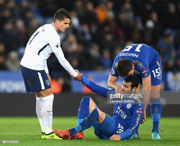 Vicente Iborra of Leicester City is helped up by Harry Maguire and Erik Lamela of Tottenham Hotspur during the Premier League match between Leicester...