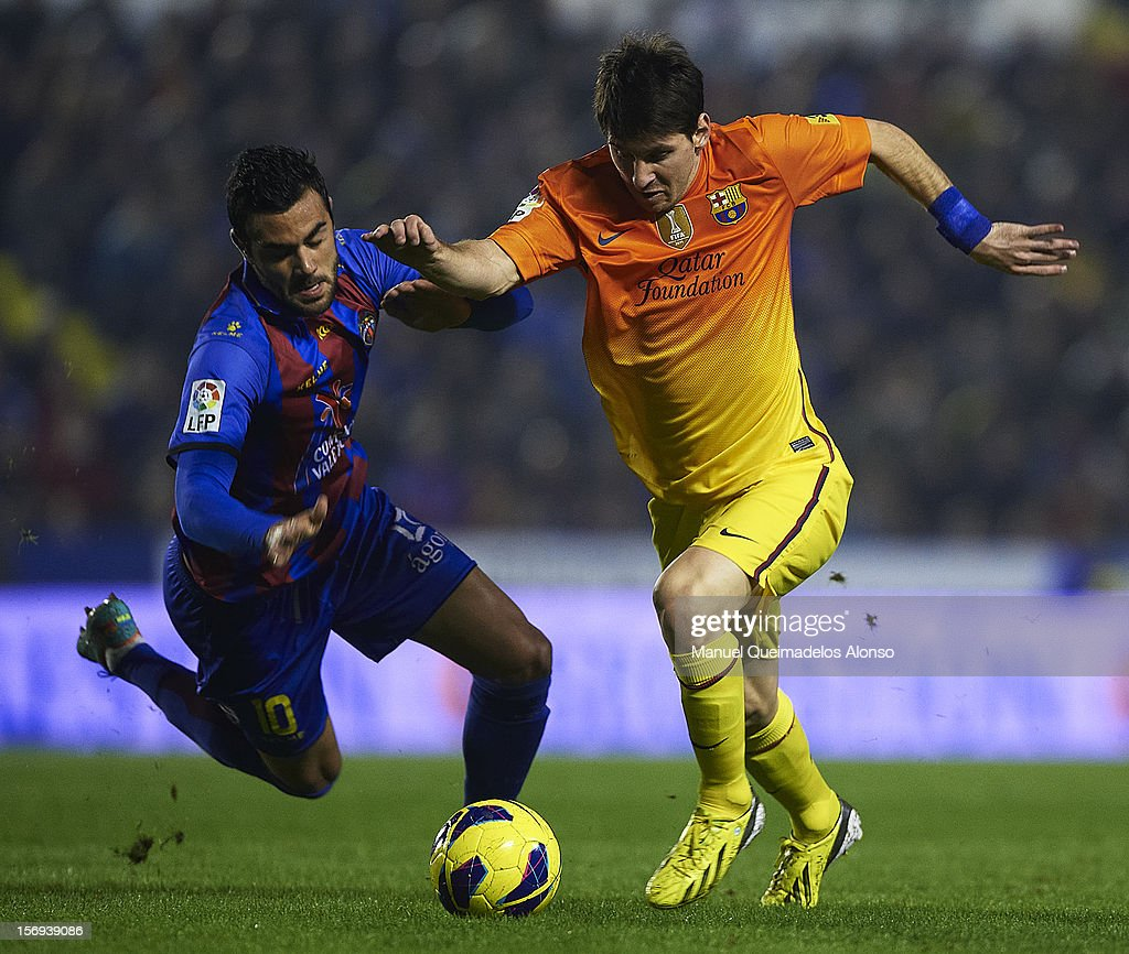 Vicente Iborra (L) of Levante competes for the ball with <a gi-track='captionPersonalityLinkClicked' href=/galleries/search?phrase=Lionel+Messi&family=editorial&specificpeople=453305 ng-click='$event.stopPropagation()'>Lionel Messi</a> of Barcelona during the la Liga match between Levante UD and FC Barcelona at Ciutat de Valencia on November 25, 2012 in Valencia, Spain.