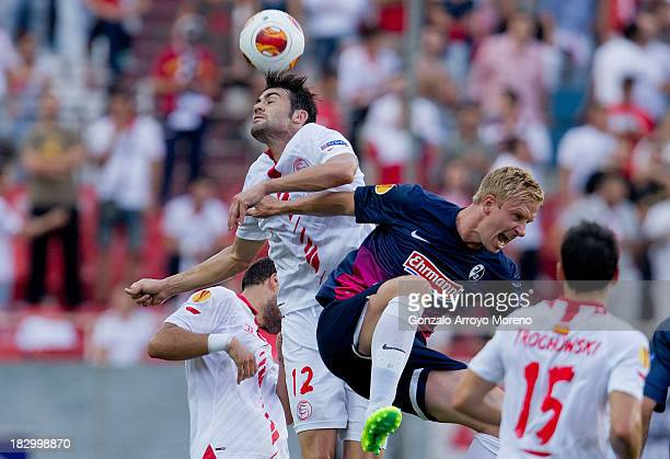 Vicente Iborra of Sevilla FC wins the header before Mike Hanke of SC Freiburg during the UEFA Europa League group H match between Sevilla FC and SC...