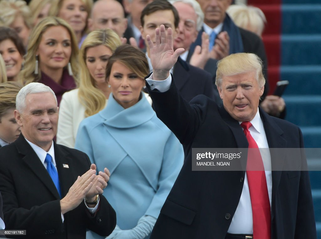TOPSHOT - Vice-president elect Mike Pence (L) applauds as President-elect Donald Trump waves to the crowd as he arrives on the platform at the US Capitol in Washington, DC, on January 20, 2017, before his swearing-in ceremony. / AFP PHOTO / Mandel NGAN