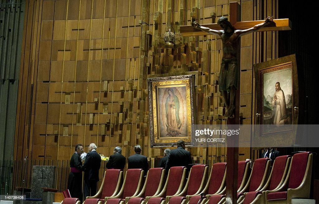 US VicePresident Joe Biden gives flowers to Mexican Monsignor Eduardo Chavez to be placed in front of an image of Virgin of Guadalupe during his...