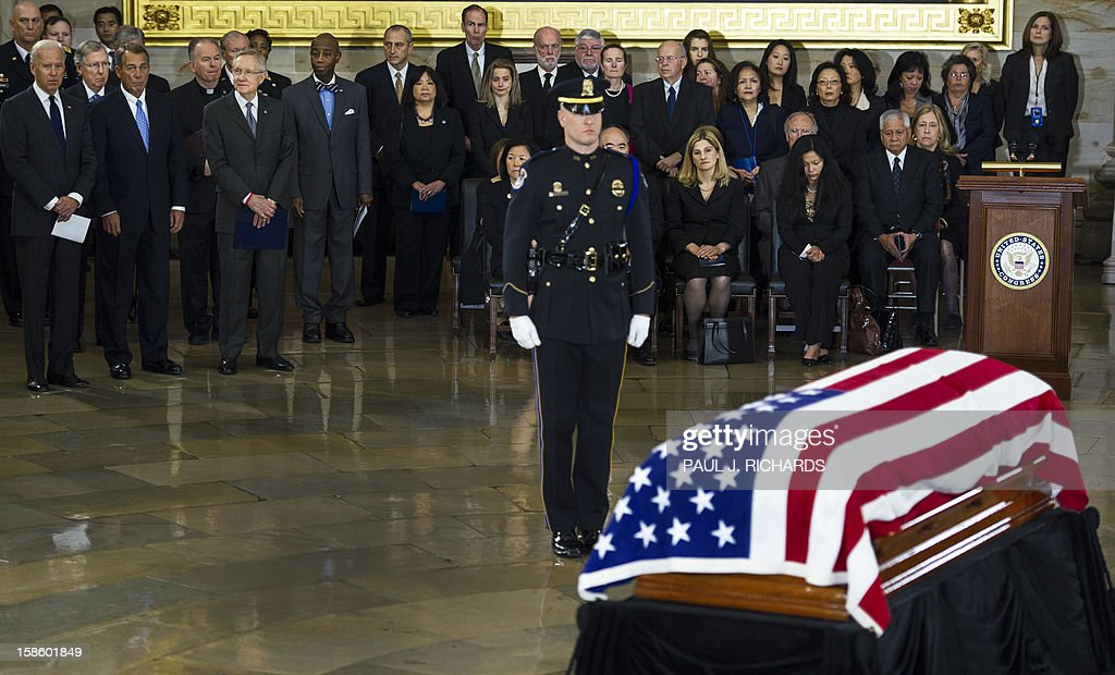 US Vice-President Joe Biden (L), US Speaker of the House John Boehner (2nd L2), US Majority Leader Harry Reid (L3), and family members( R) view the body of US Senator Daniel K. Inouye,(D-HI) as it Lies In State in a flag covered casket on the floor of the US Capitol Rotunda December 20, 2012, in Washington, DC. Inouye, one of the last World War II heroes in Congress and the longest-serving member of the US Senate, having represented Hawaii since the state joined the union in 1959, died at age 88. AFP PHOTO/Paul J. Richards
