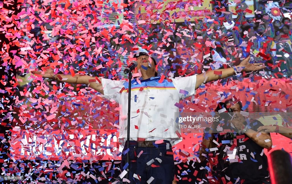 Vice-presidential candidate and son of the late dictator Ferdinand, Marcos Ferdinand Marcos Jnr., reacts as confetti rains during his 'miting-de-avance' in Manila on May 5, 2016. / AFP / TED