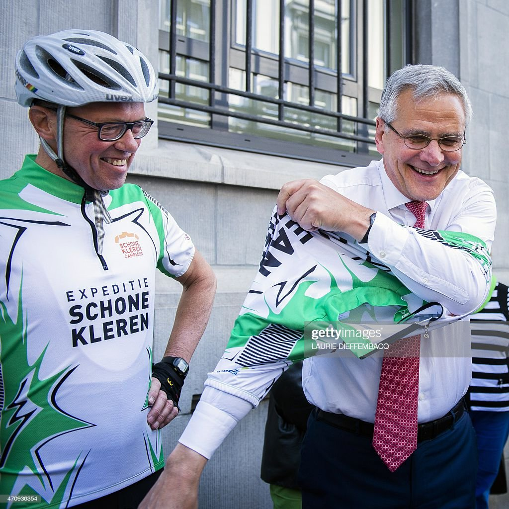 Vice-Prime Minister and Minister of Employment, Economy and Consumer Affairs <a gi-track='captionPersonalityLinkClicked' href=/galleries/search?phrase=Kris+Peeters&family=editorial&specificpeople=2203934 ng-click='$event.stopPropagation()'>Kris Peeters</a> (R) puts on a 'Clean' cycling outfit on April 24, 2015 in Brussels, as part of the 'Schone Kleren' (Clean Clothes) campaign in commemoration of the workers killed two years ago during the Rana Plaza disaster in Bangladesh.
