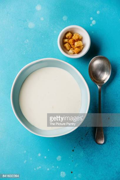 Vichyssoise cold cream soup in bowl with croutons on blue background