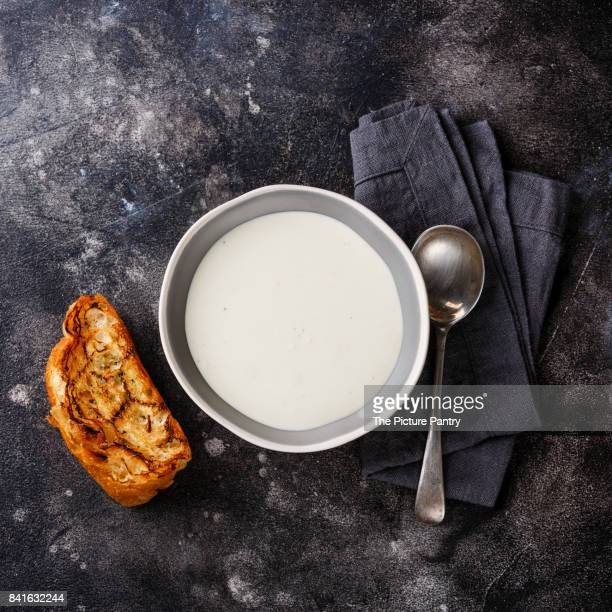 Vichyssoise cream soup in bowl with bread on dark background