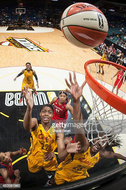 Vicki Baugh and Glory Johnson of the Tulsa Shock reach for a rebound against Tianna Hawkins of the Washington Mystics during the WNBA game on July 12...